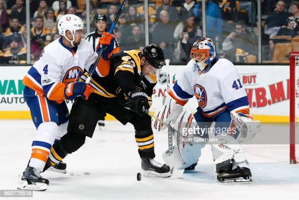 Boston Bruins center David Backes tries to find the puck as New York Islanders defenseman Dennis Seidenberg defends in front of New York Islanders...