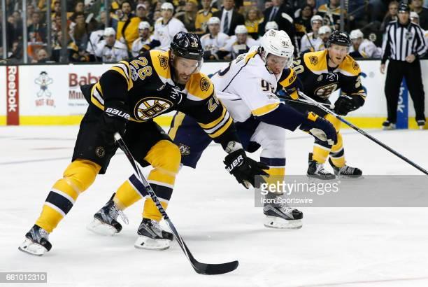Boston Bruins center Dominic Moore looks to fend off Nashville Predators center Ryan Johansen during a regular season NHL game between the Boston...