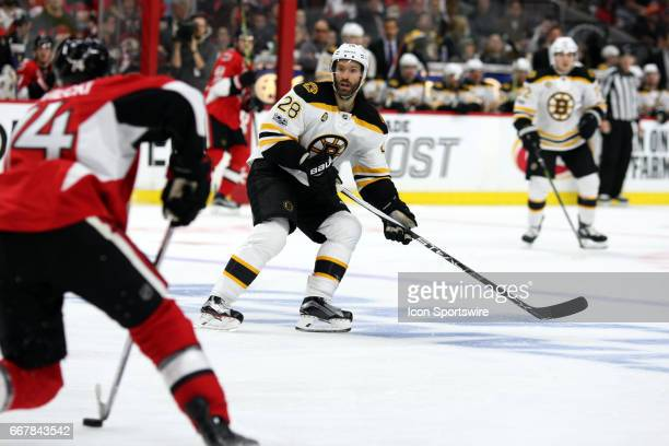 Boston Bruins Center Dominic Moore on the defensive as Ottawa Senators Defenceman Mark Borowiecki moves the puck up ice in the third period of game 1...