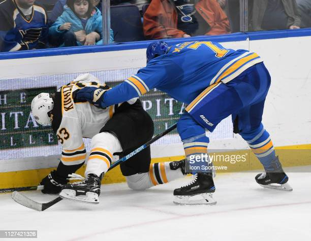 Boston Bruins center Karson Kuhlman and St Louis Blues leftwing Pat Maroon battle after a loose puck during a NHL game between the Boston Bruins and...