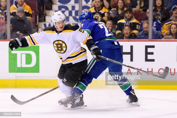 Boston Bruins center Noel Acciari is tripped up by Vancouver Canucks defenseman Ben Hutton during their NHL game at Rogers Arena on October 20 2018...