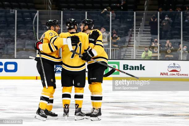 Boston Bruins center Patrice Bergeron and Boston Bruins left defenseman Jeremy Lauzon congratulate Boston Bruins left wing Taylor Hall during a game...