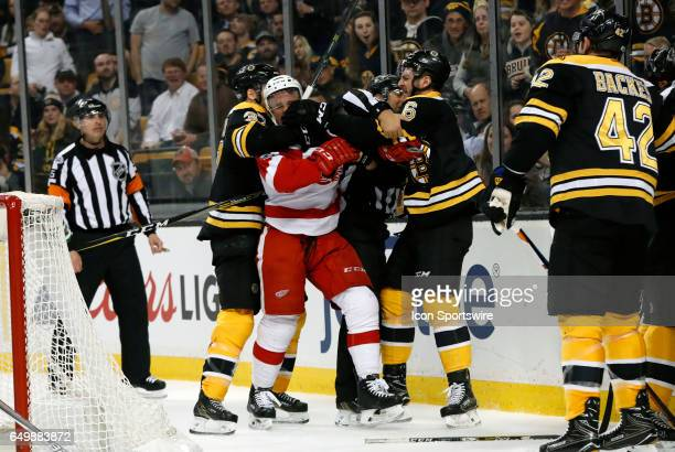 Boston Bruins center Patrice Bergeron and Boston Bruins right defenseman Colin Miller team up on Detroit Red Wings right wing Luke Glendening during...