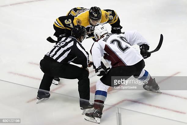 Boston Bruins center Patrice Bergeron and Colorado Avalanche center Nathan MacKinnon wait for linesman Steve Barton to drop the puck during a regular...