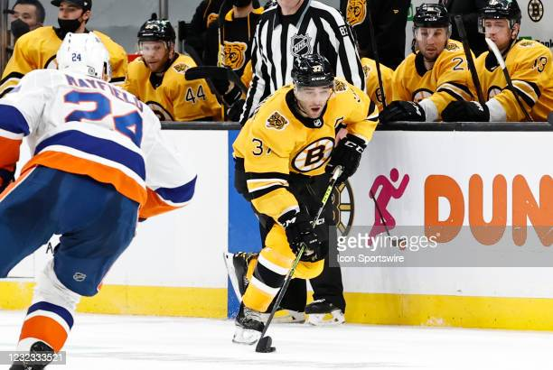 Boston Bruins center Patrice Bergeron carries the puck watched by New York Islanders defenseman Scott Mayfield during a game between the Boston...