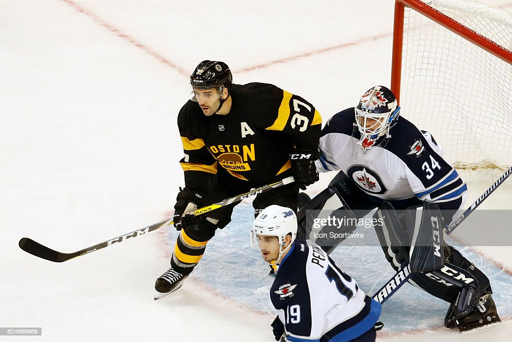 Boston Bruins center Patrice Bergeron (37) sets up in front of Winnipeg Jets goalie Michael Hutchinson (34) during a regular season NHL game between the Boston Bruins and the Winnipeg Jets on November 19, 2016, at TD Garden in Boston, Massachusetts. The Bruins defeated the Jets 4-1.