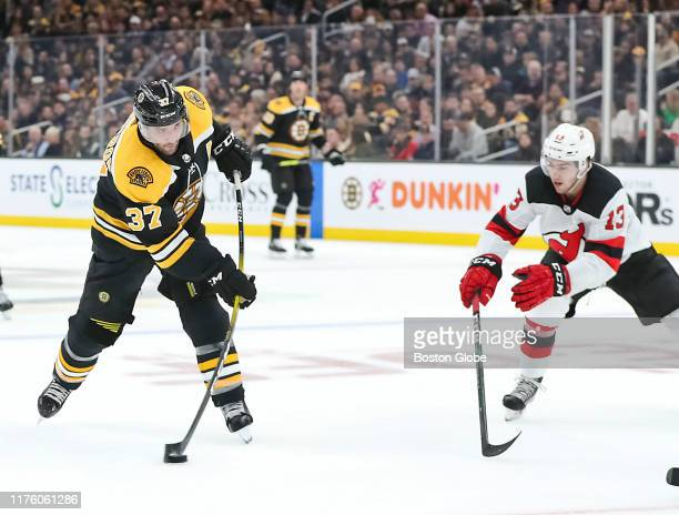 Boston Bruins center Patrice Bergeron takes a shot on goal in front of New Jersey Devils center Nico Hischier during the second period The Boston...