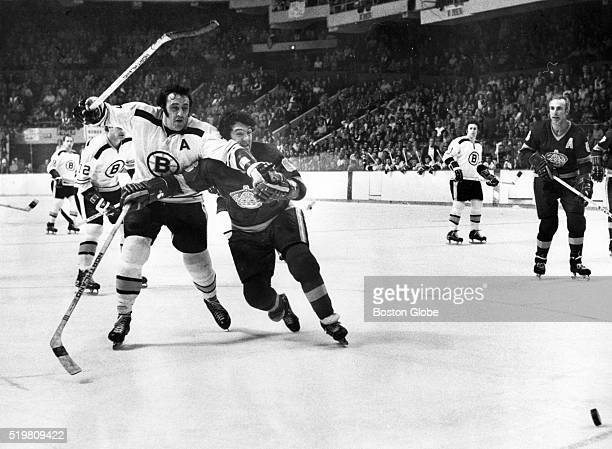 Boston Bruins center Phil Esposito left races against Paul Curtis of the Los Angeles Kings player to the puck with Harry Howell during a game at...