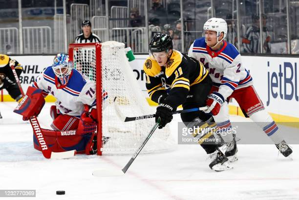 Boston Bruins center Trent Frederic slips away from New York Rangers defenseman Adam Fox during a game between the Boston Bruins and the New York...