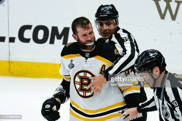 Boston Bruins' David Backes is held back by linesman Derek Amell during the third period of Game 4 of the NHL Stanley Cup Finals hockey game between...