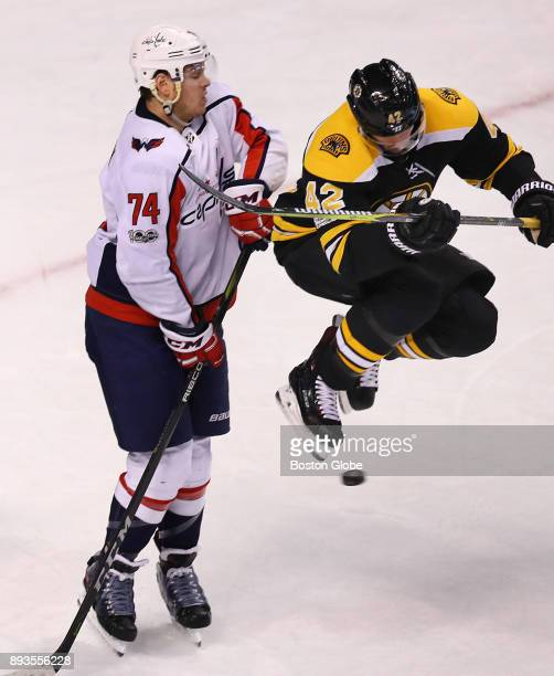 Boston Bruins' David Backes jumps high in front of Capitals' John Carlson to avoid a slapshot at the Capitals net in the second period The Boston...