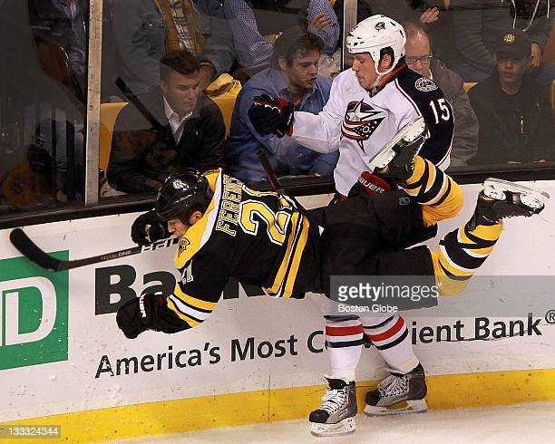 Boston Bruins defenseman Andrew Ference takes a big hit along the boards from Columbus Blue Jackets right wing Derek Dorsett during the first period...