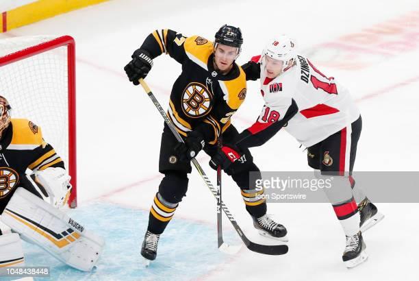 Boston Bruins defenseman John Moore holds off Ottawa Senators left wing Ryan Dzingel during a game between the Boston Bruins and the Ottawa Senators...
