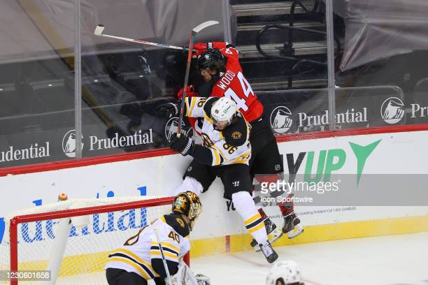 Boston Bruins defenseman Kevan Miller hits New Jersey Devils left wing Miles Wood during the National Hockey League game between the New Jersey...
