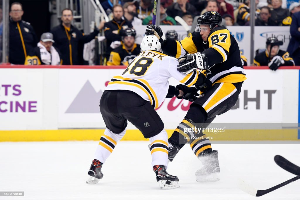 Boston Bruins Defenseman Matt Grzelcyk (48) checks Pittsburgh Penguins Center Sidney Crosby (87) off the puck during the second period in the NHL game between the Pittsburgh Penguins and the Boston Bruins on January 7, 2018, at PPG Paints Arena in Pittsburgh, PA.