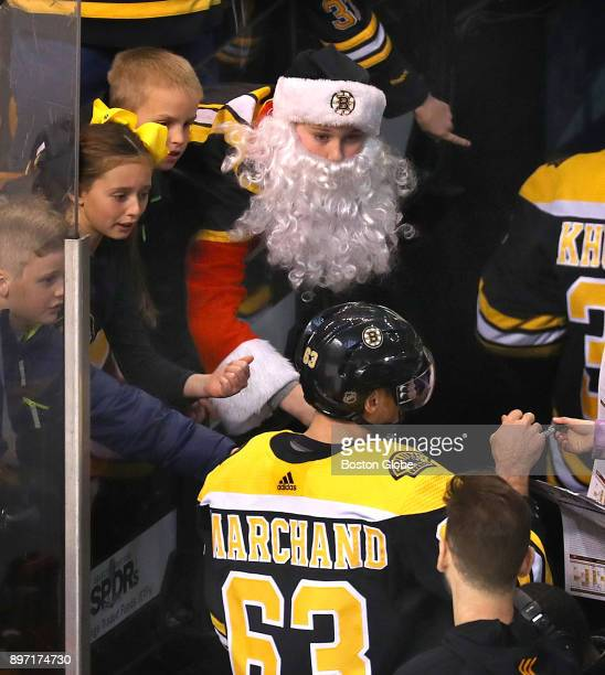 Boston Bruins fans including one dressed as Santa Claus reach down as they try to get an autograph from Bruins' Brad Marchand after pregame warmups...
