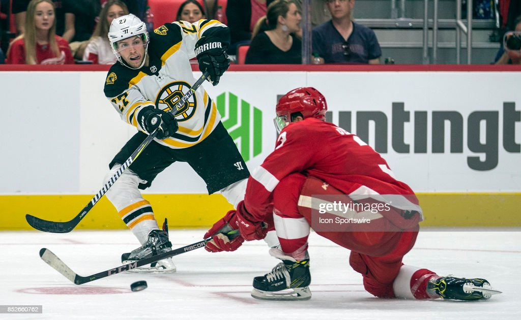 Boston Bruins forward Austin Czarnik (27) shoots the puck past Detroit Red Wings defenseman Nick Jensen (3), in the third period of the Boston Bruins at Detroit Red Wings pre-season NHL hockey game on September 23, 2017 at Little Caesars Arena, in Detroit, MI. The Red Wings won 5-1.