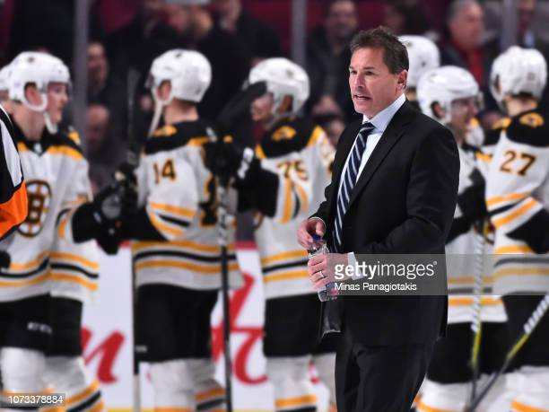 Boston Bruins head coach Bruce Cassidy walks past his team as they celebrate their victory against the Montreal Canadiens during the NHL game at the...
