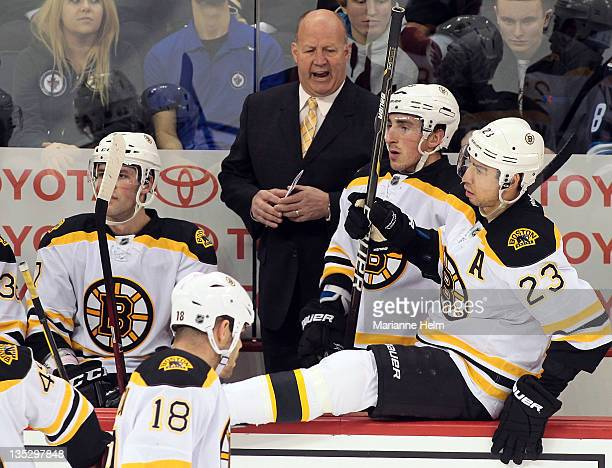 Boston Bruins' head coach Claude Julien talks to players Brad Marchand and Chris Kelly on the bench in NHL action at the MTS Centre on December 6...