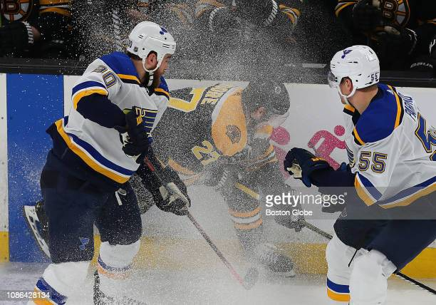 Boston Bruins' John Moore in lost in a blizzard of ice as he fights for a loose puck along the boards in the first period with the Blues' Ryan...