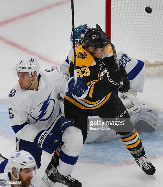 Boston Bruins' Karson Kuhlman fights for position in front of the Lightning net with the Lightning's Dan Girardi as the puck fired by the Bruins'...
