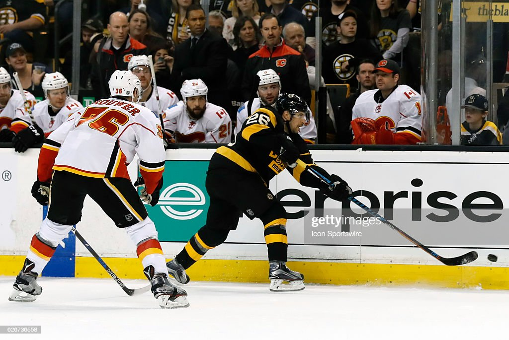 Boston Bruins left defenseman John-Michael Liles (26) plays the puck along the boards as Calgary Flames right wing Troy Brouwer (36) moves in during a regular season NHL game between the Boston Bruins and the Calgary Flames on November 25, 2016, at TD Garden in Boston, Massachusetts. The Flames defeated the Bruins 2-1.