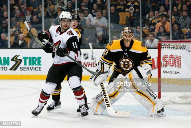 Boston Bruins left defenseman Torey Krug ties up Arizona Coyotes left wing Brendan Perlini in front of Boston Bruins goalie Tuukka Rask during a game...