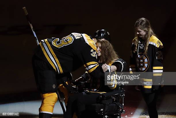 Boston Bruins left defenseman Zdeno Chara hugs Denna Laing as her sister Lexie looks on before a regular season NHL game between the Boston Bruins...