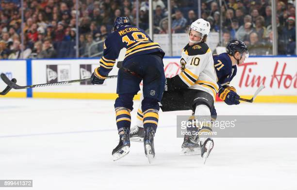 Boston Bruins left wing Anders Bjork is hit by Buffalo Sabres defenseman Jake McCabe and Buffalo Sabres left wing Evan Rodrigues during an NHL game...