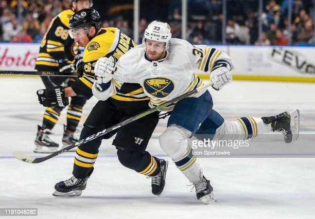 Boston Bruins left wing Brad Marchand and Buffalo Sabres defenseman Colin Miller fight for the puck during a game between the Boston Bruins and the...