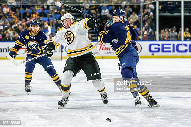 Boston Bruins Left Wing Brad Marchand and Buffalo Sabres Defenseman Brendan Guhle fight for puck while Buffalo Sabres Left Wing William Carrier looks...
