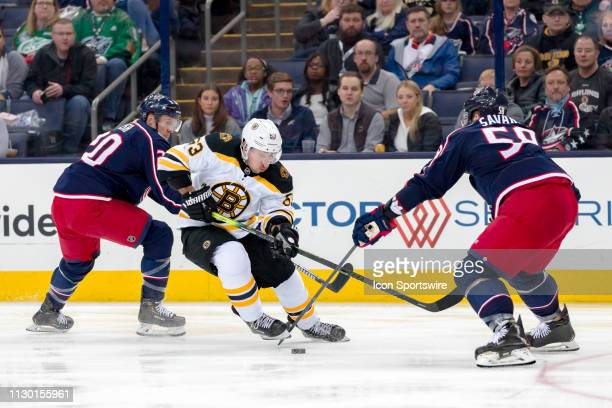 Boston Bruins left wing Brad Marchand has pressure from Columbus Blue Jackets center Riley Nash and Columbus Blue Jackets defenseman David Savard in...