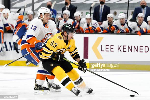 Boston Bruins left wing Brad Marchand holds off New York Islanders center Mathew Barzal during a game between the Boston Bruins and the New York...