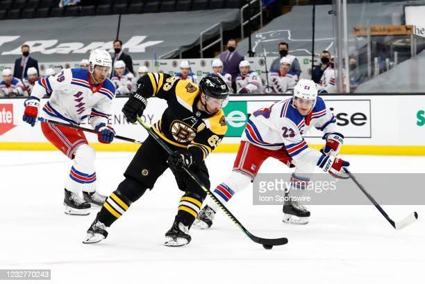 Boston Bruins left wing Brad Marchand slips between New York Rangers defenseman K'Andre Miller and New York Rangers defenseman Adam Fox during a game...