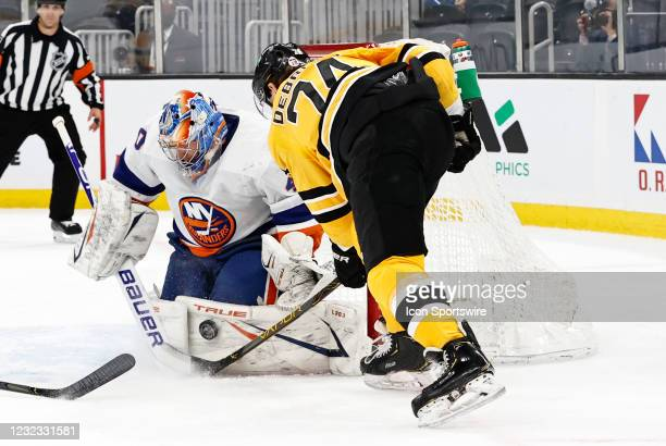 Boston Bruins left wing Jake DeBrusk digs for the puck off the pads of New York Islanders goalie Semyon Varlamov during a game between the Boston...