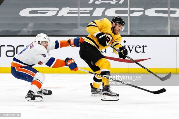 Boston Bruins left wing Taylor Hall shoots and scores besting New York Islanders defenseman Adam Pelech during a game between the Boston Bruins and...