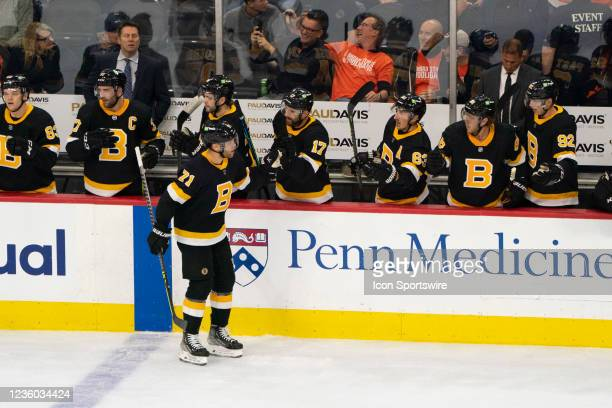 Boston Bruins Left Wing Taylor Hall skates by the bench and is congratulated by teammates for scoring a goal during the second period of a National...
