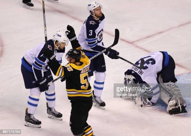 Boston Bruins' Noel Acciari celebrates teammate Torey Krug's third period goal that got past Jets goalie Connor Hellebuyck Jets' Ben Chiarot left and...