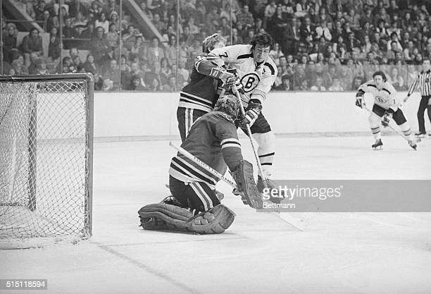 Bruins' Phil Esposito tries to muscle his way past Black Hawks defenseman Pat Stapleton to get at puck which is grabbed by Black Hawks' goalie Gary...