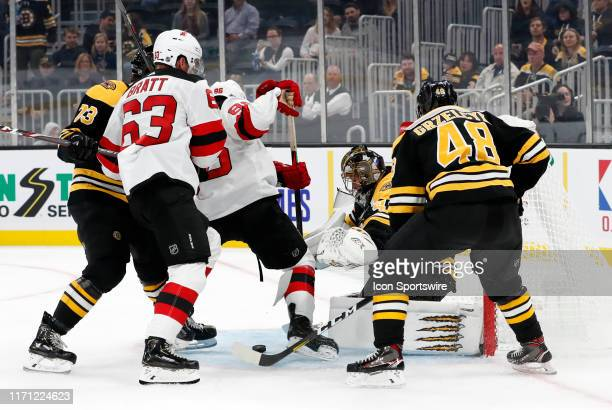 Boston Bruins right defenseman Charlie McAvoy ties up New Jersey Devils center Jack Hughes with the puck loose in front of Boston Bruins goalie...