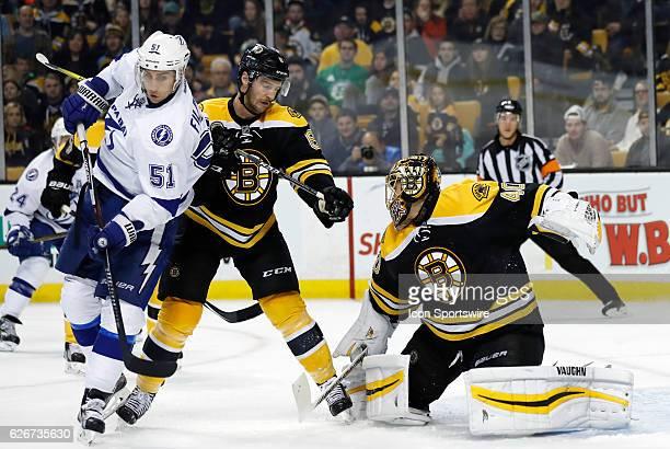Boston Bruins right defenseman Colin Miller clears out Tampa Bay Lightning center Valtteri Filppula as Boston Bruins goalie Tuukka Rask makes a right...
