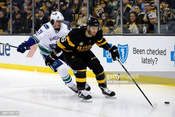 Boston Bruins right defenseman Colin Miller holds off Vancouver Canucks left wing Loui Eriksson during a regular season NHL game between the Boston...