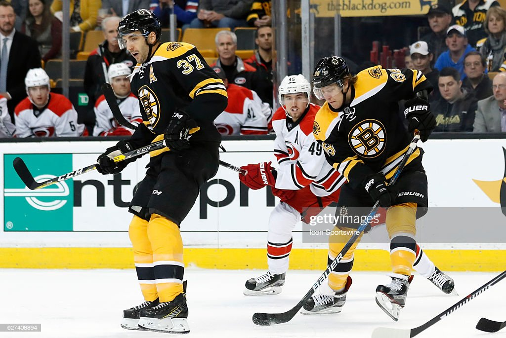 Boston Bruins right wing David Pastrnak (88) picks up a loose puck behind Boston Bruins center Patrice Bergeron (37) during a regular season NHL game between the Boston Bruins and the Carolina Hurricanes on December 1, 2016, at TD Garden in Boston, Massachusetts. The Bruins defeated the Hurricanes 2-1 (SO).