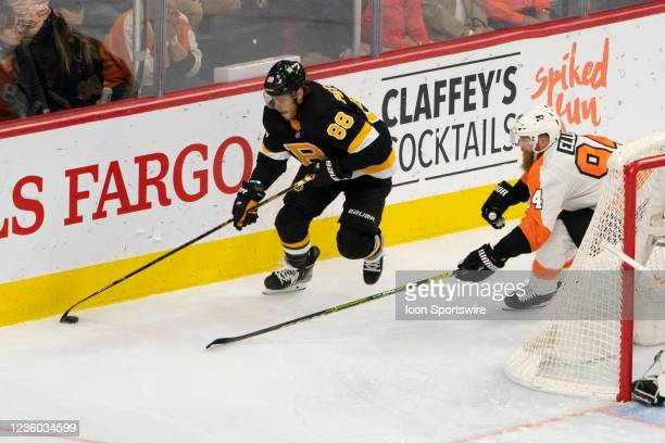 Boston Bruins Right Wing David Pastrnak skates with the puck with Philadelphia Flyers Defenseman Ryan Ellis defending during the second period of a...