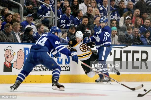 Boston Bruins Right Winger David Pastrnak is taken down against the boards by Toronto Maple Leafs Center Nazem Kadri during the regular season NHL...