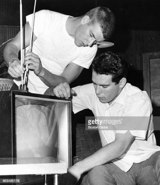 Boston Bruins rookies Bobby Orr left and Joe Watson right adjust their television set inside their apartment in Nahant Mass Oct 24 1966
