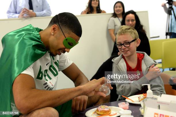 Boston Celtic Jayson Tatum decorates donuts with Matthias during Day of Joy Celebration at Boston Children's Hospital August 28 2017 in Boston...