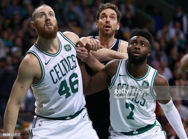 Boston Celtics' Aron Baynes left and Jaylen Brown right surround the Spurs' Pau Gasol under the basket during the first half The Boston Celtics host...