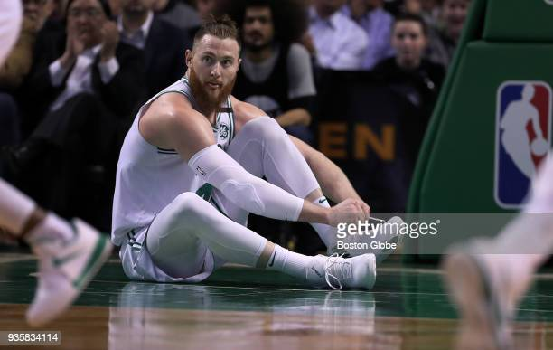 Boston Celtics' Aron Baynes ties one of his sneakers after it came off under the basket in the first half The Boston Celtics host the Oklahoma City...