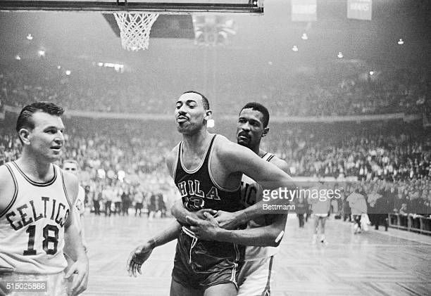 Boston: Celtics' Bill Russell pins Warriors' Wilt Chamberlain's right arm, and holds him, during wild 4th quarter in which both sides fought. Boston...